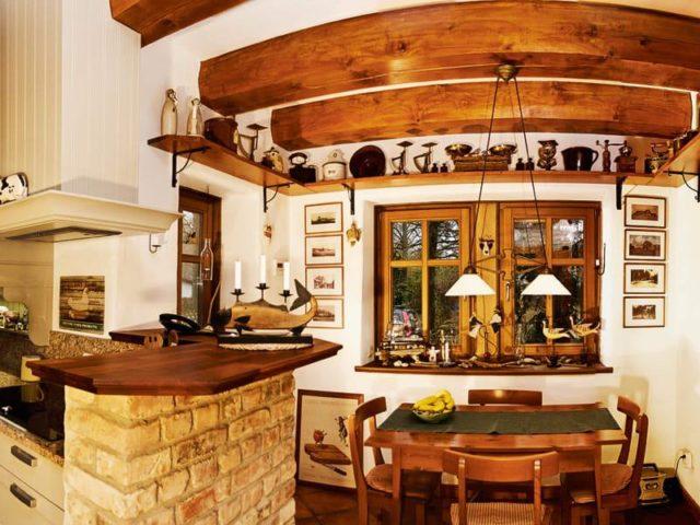 Der aus rustikalen Klinkern gemauerte Küchentresen passt perfekt zur Balkendecke.