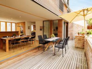 Holzterrasse, die den Wohnraum nach außen erweitert