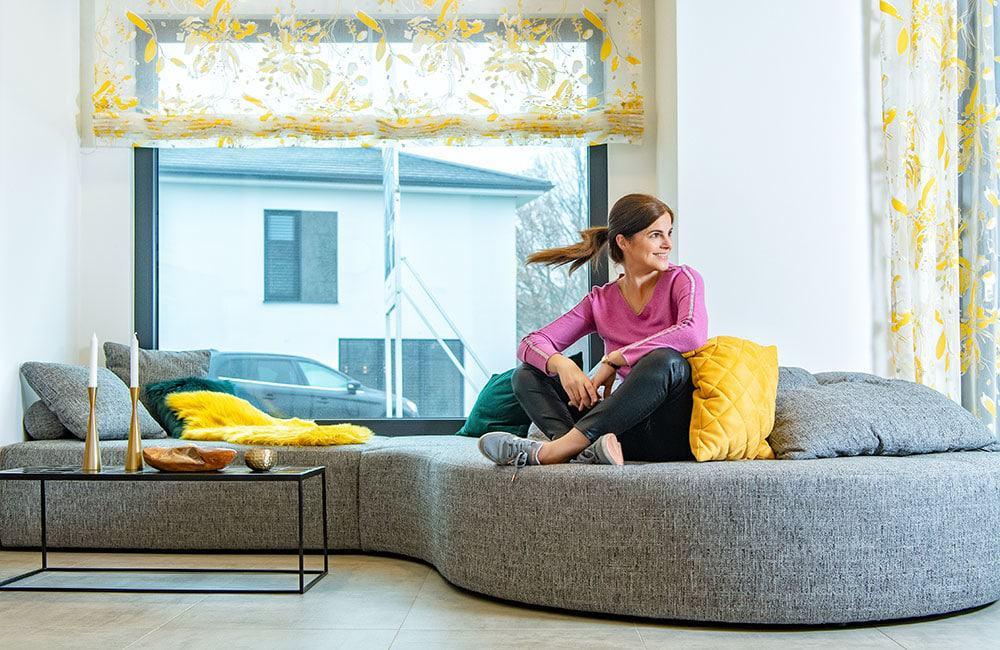 Im Wohnzimmer ersetzt eine Fenstercouch die übliche Polstergarnitur. Fenster, Wand und Kuschelkissen statt Sofalehne. Musterhaus Concept-M 163 Dresden von Bien-Zenker