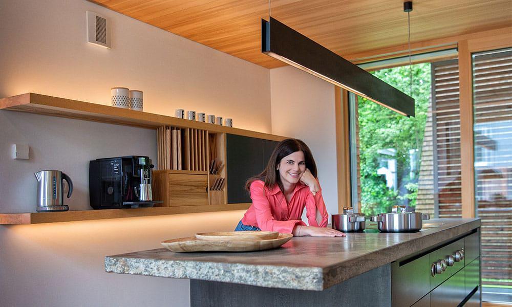 Stilvoll und einladend: Echtholz und Echtstein prägen die Küche des Musterhauses Alpenchic von Baufritz im Bauzentrum Poing bei München. (Foto: zuhause3.de)