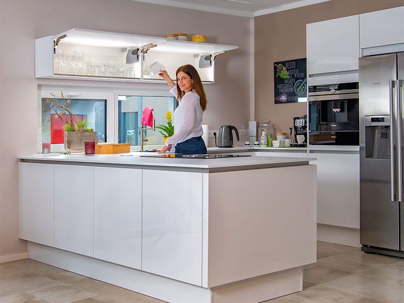 Praktisch und schön: beleuchtete Hängeschränke in optimaler Greif-Höhe und viel Stauraum in der Kücheninsel. Musterhaus Ravenna von Helma (Foto: zuhause3.de)