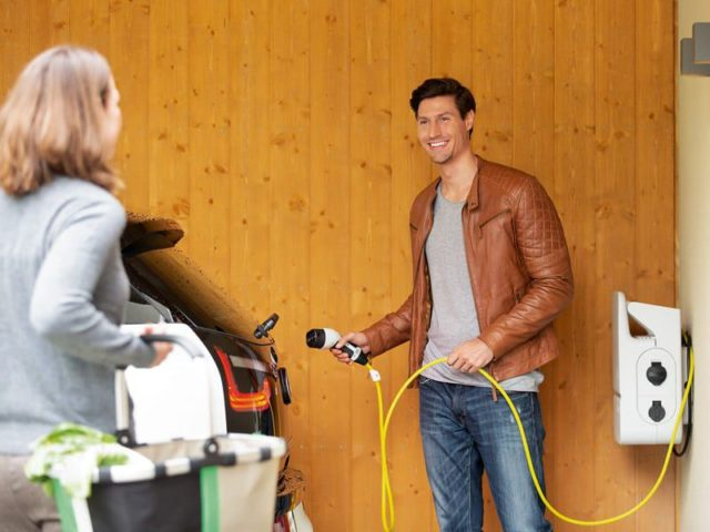 Mann tankt sein Elektroauto auf.