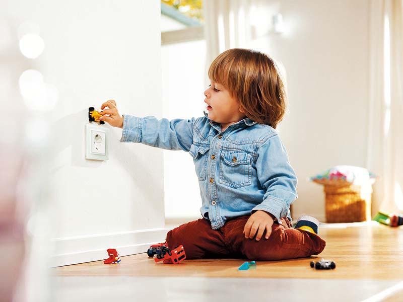 Kind spielt an einer Steckdose