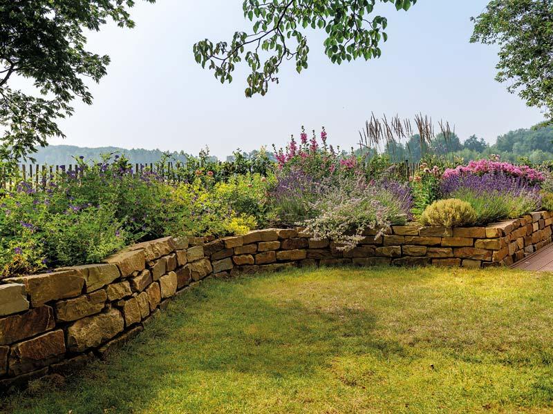 Die roughen Steine einer Trockenmauer erzeugen im Garten Landgartencharme.