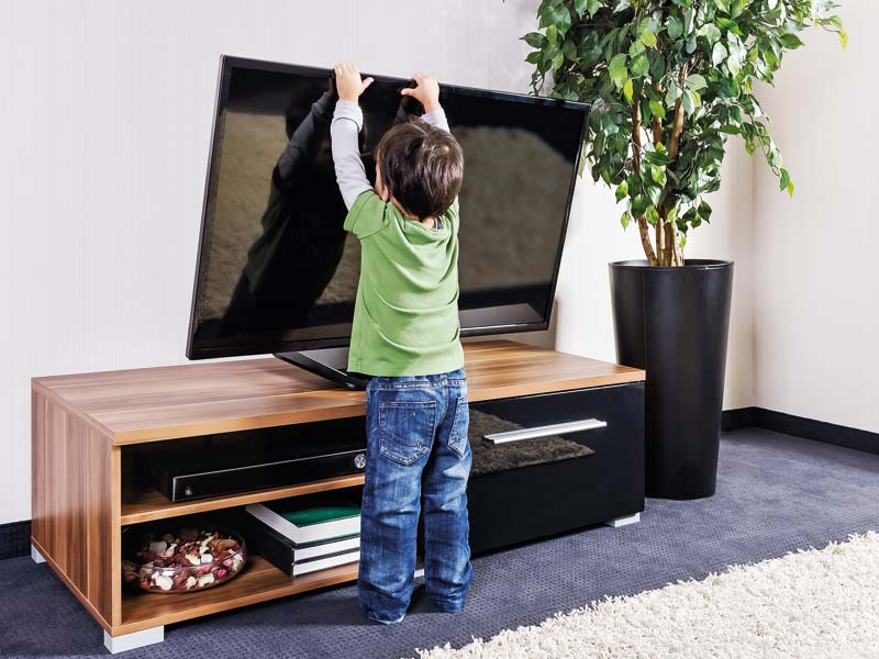 Kind zieht an einem Flachbildfernseher.