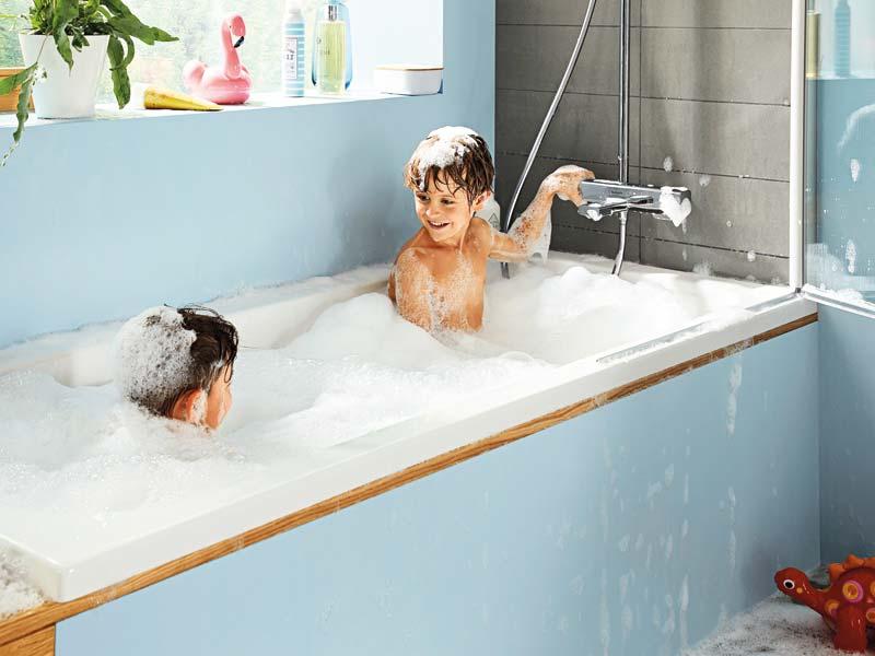 Kinder in der Badewanne fassen an eine Armatur.