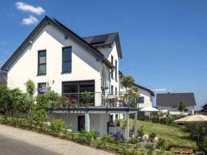 Haus Steinmann von Baumeisterhaus. Außenansicht mit Balkon und überdachter Terrasse.