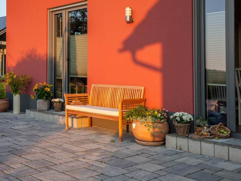 Haus Urban von Baumeisterhaus. Eingangsbereich mit Bank in der Abendsonne.