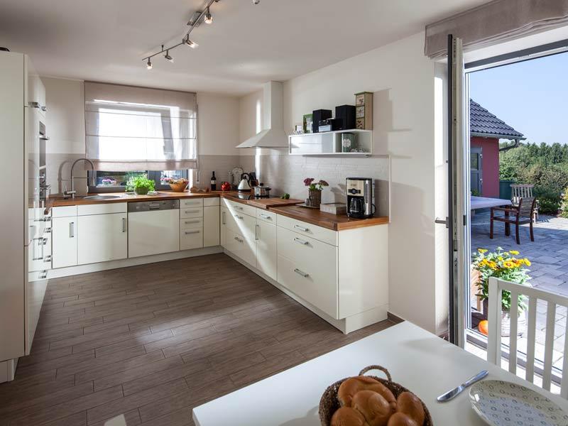 Haus Urban von Baumeisterhaus. Blick in die Küche und raus auf die Terrasse.