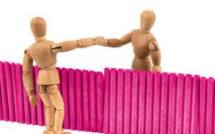 Zwei Holzpuppen reichen sich die Hand über den Zaun.