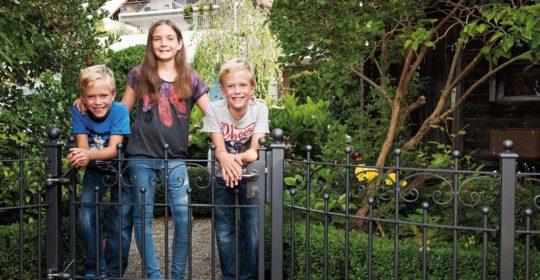 Kinder vor einem Metallzaun